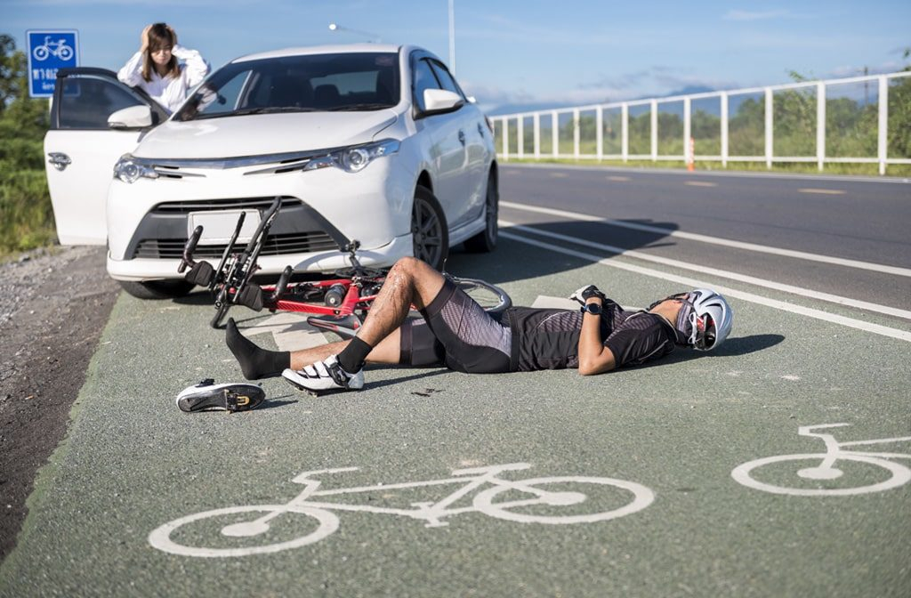 Bicycle accident injury lawyer, man laying on floor after being hit by car